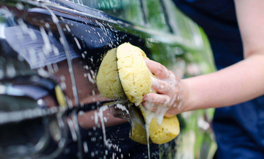 scrubbing car exterior with sponge